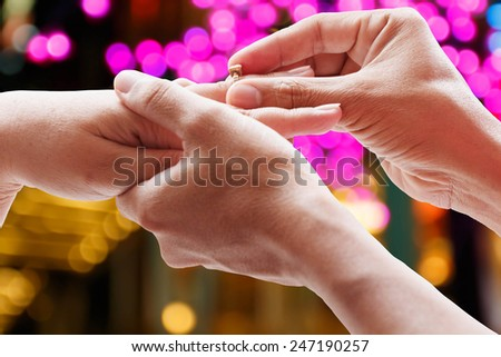 closeup groom wearing wedding ring on bride,valentine day concept - stock photo