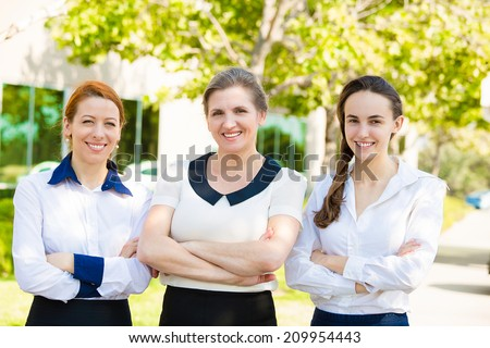 Closeup Group portrait of Three confident business women smiling, two generation corporate workers, senior company boss, young employees, outdoors street background. Positive face expressions emotions - stock photo