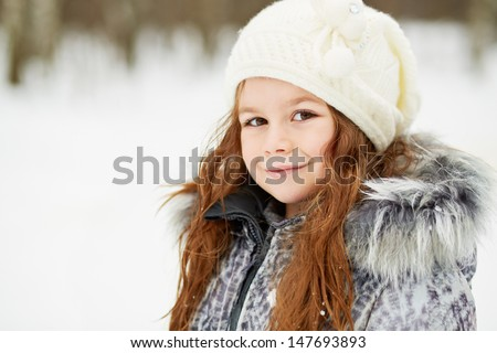Closeup half-turned portrait of little girl in grey jacket with fur collar and knitted hat in snowy park - stock photo