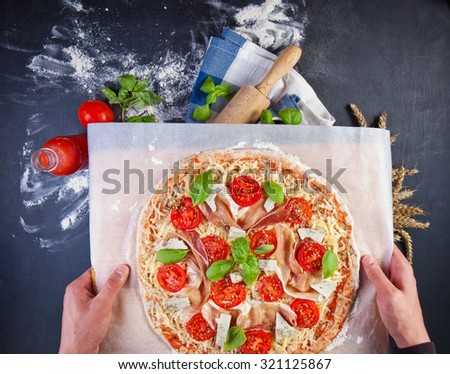 Closeup hand of baker making pizza at kitchen - stock photo