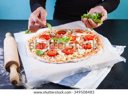 Closeup hand of baker making pizza at kitchen - stock photo