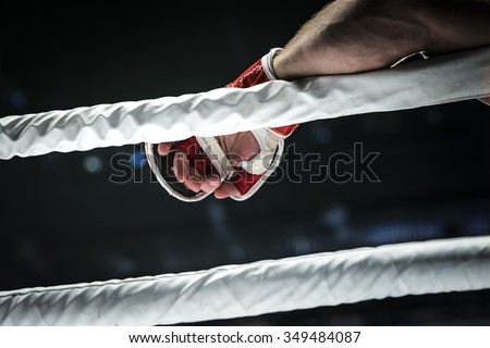 closeup hand of fighter MMA in glove lays ropes of ring - stock photo