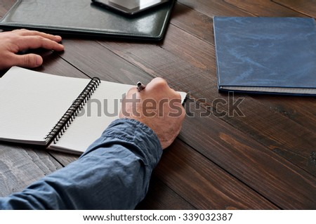 Closeup hand of man writing something in blank notebook on wooden table. Top view. Copy space - stock photo