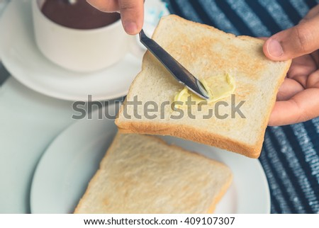 Closeup hand of young woman preparing breakfast toast with butter. - stock photo