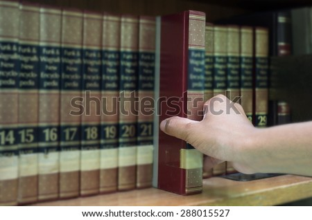 closeup hand selecting book from a bookshelf in library - stock photo