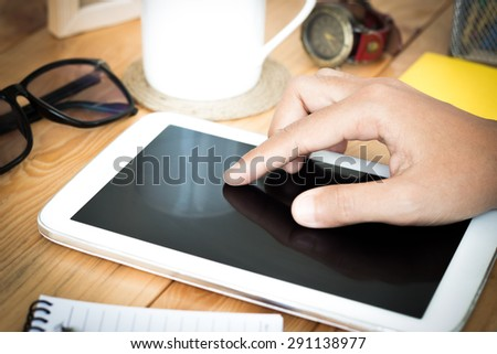 closeup hand using digital tablet on workspace - stock photo