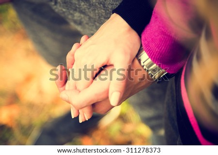 Closeup Hands of a Couple Held Together on Autumn Background. Toned Photo with Shallow Depth of Field. Focus on Ring. - stock photo