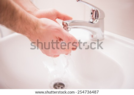 Closeup hands of man is washing hands under running water. - stock photo
