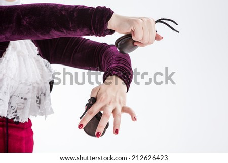 closeup hands with castanets of a female spanish flamenco dancer in white blouse and vinous flamenco skirt in studio on gray background - stock photo