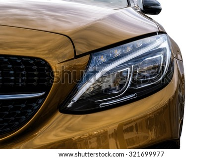 Closeup headlights of yellow car and Car exterior detail with White back. Closeup headlights of car. Modern luxury car close-up banner background. Concept of expensive, sports auto Closeup headlights - stock photo