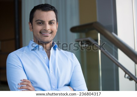 Closeup headshot portrait, happy handsome business man, smiling, arms crossed in blue shirt,confident and friendly on isolated office interior background. Corporate success - stock photo