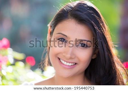 Closeup headshot portrait of confident smiling happy pretty young woman, isolated background of blurred trees, flowers. Positive human emotion facial expression feelings, attitude, perception - stock photo