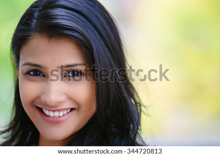 Closeup headshot portrait of confident smiling happy pretty young woman, isolated background of blurred trees. Positive human emotion facial expression feelings, attitude, perception - stock photo