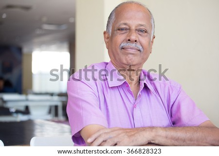 Closeup headshot portrait of elderly gentleman arms crossed folded, in pink shirt smiling, content, isolated sitting indoors background  - stock photo
