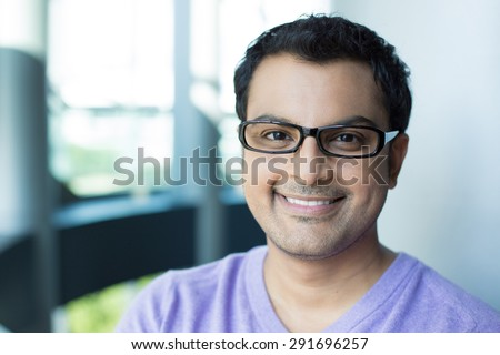 Closeup headshot portrait, smiling happy handsome man in purple sweater v-neck, wearing black glasses, isolated inside office background. - stock photo