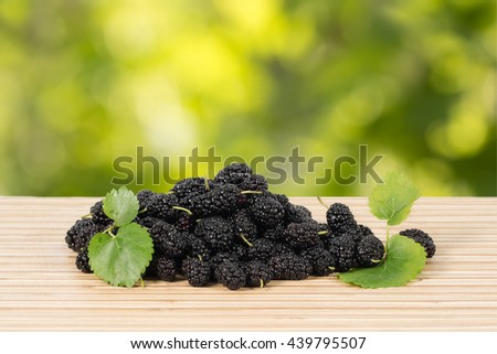 Closeup heap of ripe black mulberries with green leaves on table on green leaves background. Horizontal composition - stock photo