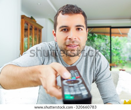 Closeup hispanic male wearing light blue sweater holding up remote control in front of camera, funny angle. - stock photo