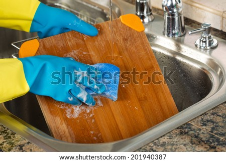 Closeup horizontal image of hands wearing rubber gloves washing bamboo cutting board with sponge and soapy water inside of kitchen sink  - stock photo