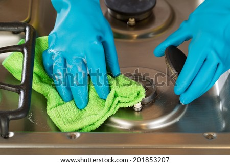 Closeup horizontal image of hands wearing rubber gloves while removing soap from stove top range green with microfiber rag  - stock photo