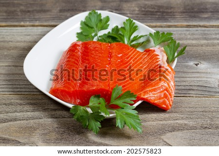 Closeup horizontal photo of fresh red salmon fillet on white plate with parsley on the side and rustic wood underneath  - stock photo