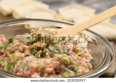 Closeup horizontal photo of homemade traditional Chinese Dumpling ingredients in glass bowl with completed wrapped dumplings in background   - stock photo