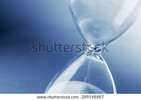 Closeup hourglass clock on light blue background - stock photo
