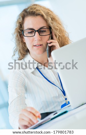 Closeup image of a businesswoman on the phone while making notes on the foreground  - stock photo