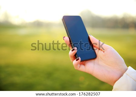 Closeup image of a female hand holding smartphone - stock photo
