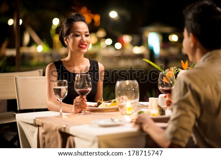 Closeup image of a happy young woman at a date with her boyfriend on the foreground  - stock photo