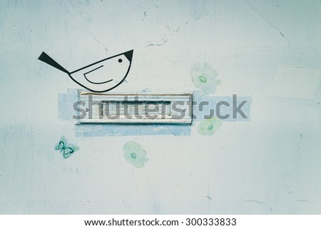 Closeup image of a letterbox slot in a light-blue door. Around the slot a cute bird, a butterfly and some flowers. The slot is sealed with tapes. - stock photo