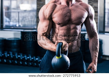 CLoseup image of a man doicing exercise with kette ball in gym - stock photo