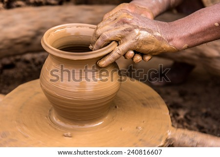 Closeup image of a potter's hands shaping soft clay to make an earthen pot - stock photo