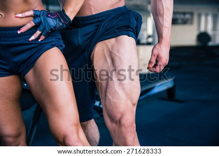 Closeup image of a strong woman and muscular man posing at gym - stock photo