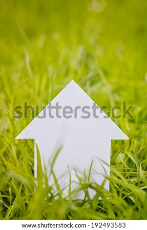 Closeup image of a white paper cutout house among fresh and green spring grass with copy space above it. - stock photo