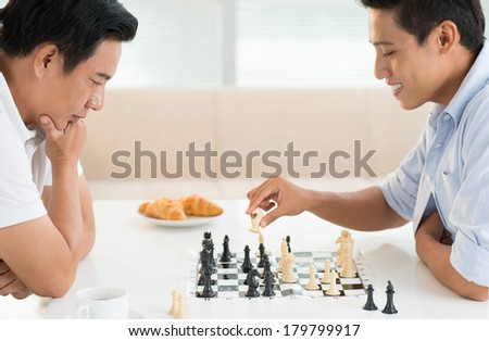 Closeup image of a young guy and his father having chess competition at home  - stock photo