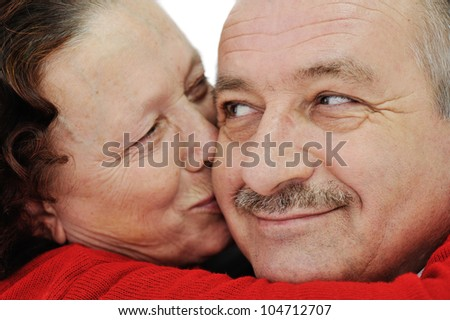 Closeup image of elderly woman kissing in a cheek her husband - stock photo