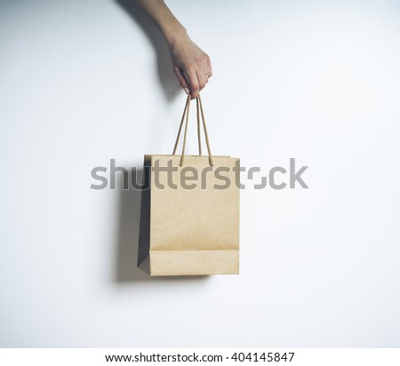 Closeup image of female hand holding blank craft package, mockup of brown paper shopping bag with handles - stock photo