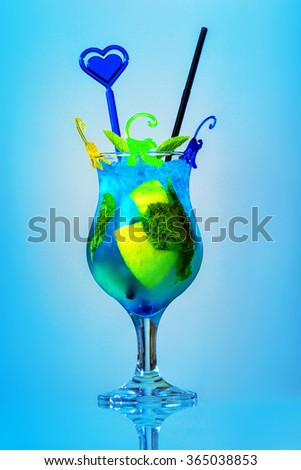 Closeup image of fresh alcohol cocktail with blue curacao, lime and ice isolated at blue background. - stock photo