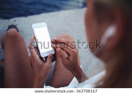 Closeup image of hipster girl chatting on cell telephone with blank copy space screen for your text message or promotional content, woman using mobile phone while sitting on concrete pier near the sea - stock photo