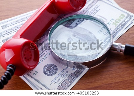 Closeup image of magnifying glass on hundred dollar bills with a red telephone receiver on wooden table. Selective focus. - stock photo