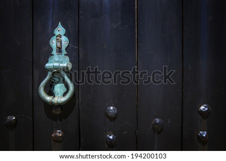 Closeup image of old wooden door with metal knob and rusty bolt. - stock photo