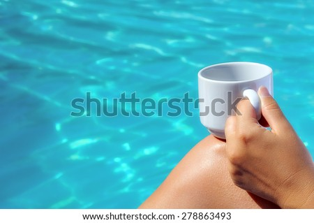 Closeup image of real attractive female beauty holding cup of coffee near swimming pool - stock photo