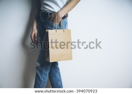 Closeup image of young woman with craft paper bag, mock-up of brown paper package with handles - stock photo