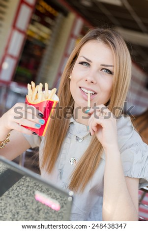closeup image on beautiful blond young woman with green eyes having fun happy smiling & looking into the camera eating french fries in fast food coffee shop or restaurant  - stock photo