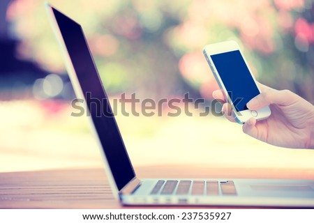 Closeup image woman hands holding, using smart, mobile phone and computer isolated outside city background. New generation technology, people addiction concept. Customer service provider relationship - stock photo