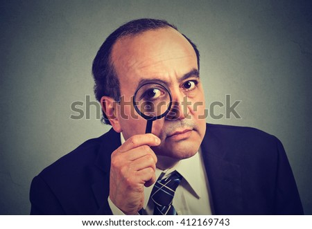 Closeup investigator business man looking with magnifying glass isolated on gray wall background  - stock photo