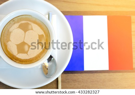 Closeup latte art of football ball next to flag of France  - stock photo