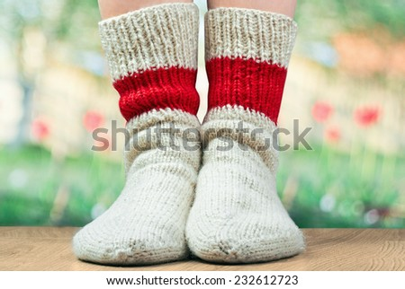 closeup  legs with pair wool knitted socks. Green grass behind - stock photo