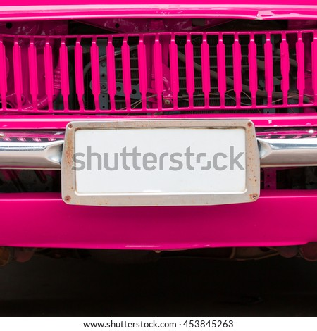 Closeup license plate at the in front of vintage pink car. - stock photo