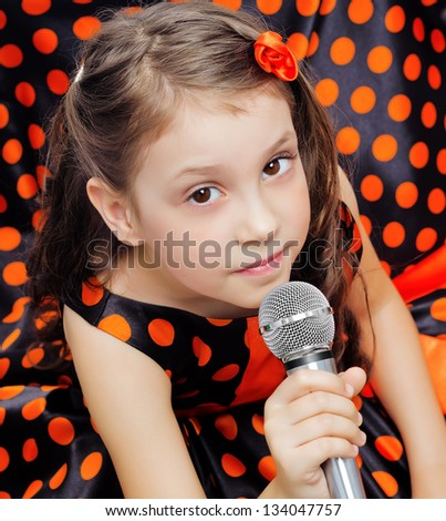 Closeup little girl in orange peas dress with microphone - stock photo